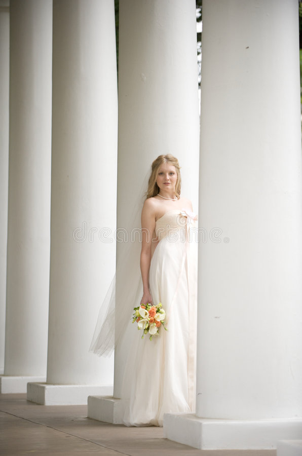 Natural bride posing in columns royalty free stock photography