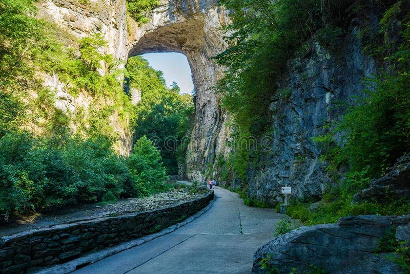 Visitors under the Rock Arch at Natural Bridge State Park, Virginia, USA. Natural Bridge State Park, Rockbridge County, VA – August 24th: Visitors royalty free stock image
