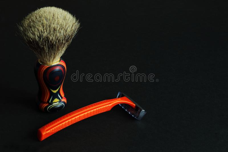 Natural bristle shaving brush with bright wooden handle and manual razor on black background. Minimal style. Concept — beauty stock image