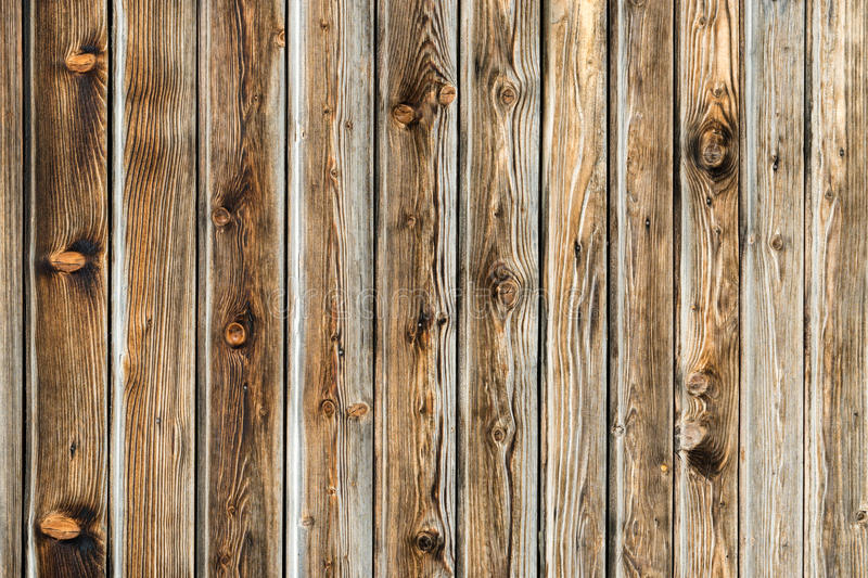 Natural brown barn wood wall. Wooden textured background pattern. Natural brown barn wood wall. Wooden wall background design. Wood planks, boards are old with royalty free stock photography
