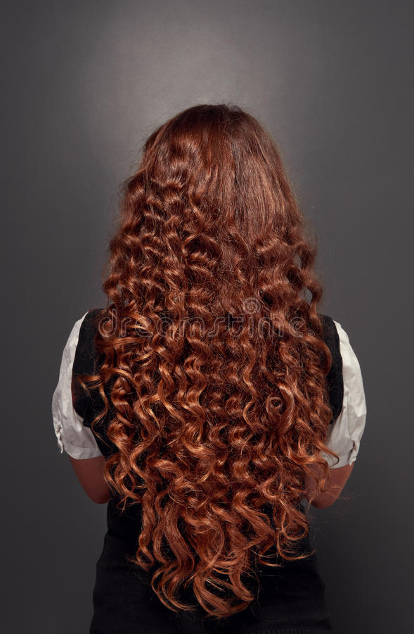 Natural brunette with long curly hair. Back view of beautiful natural brunette with long curly hair. studio shot over dark background stock photo