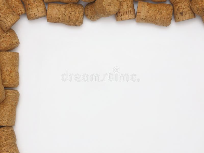 Natural Champagne or Sparkling Wine Corks Framing a White Background. Loose champagne or sparkling wine corks in nice condition line the top and left edges of a royalty free stock images