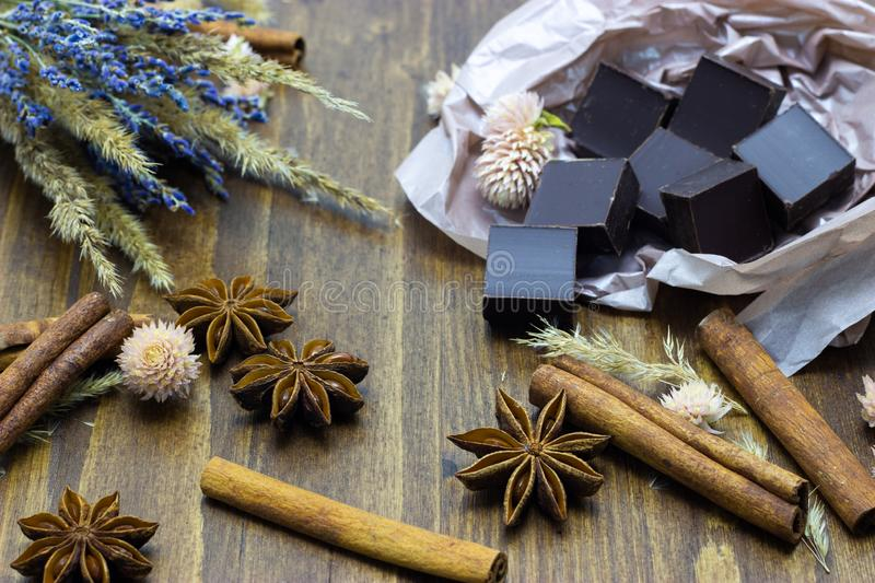 Natural chocolate with lavender flowers cinnamon and star anise on a wooden background stock photography