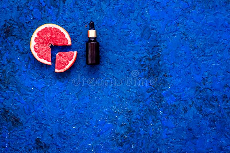 Natural citrus cosmetics with grapefruit oil on blue background top view space for text royalty free stock image