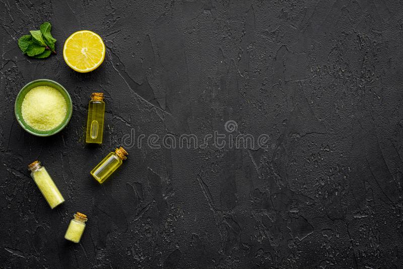 Natural citrus cosmetics. Spa oil near lemon on black background top view mock-up stock photo