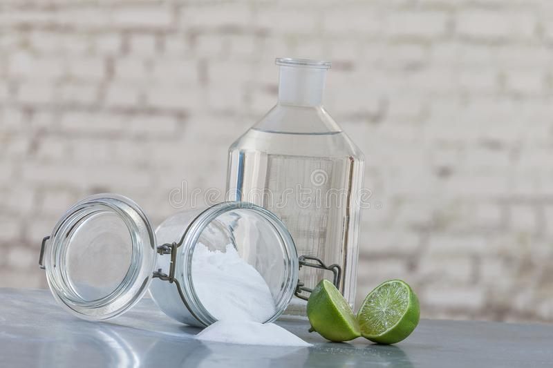 Natural cleaning products, including sodium bicarbonate, invert jar, baking soda, lemon, vinegar,on grey table on old royalty free stock image