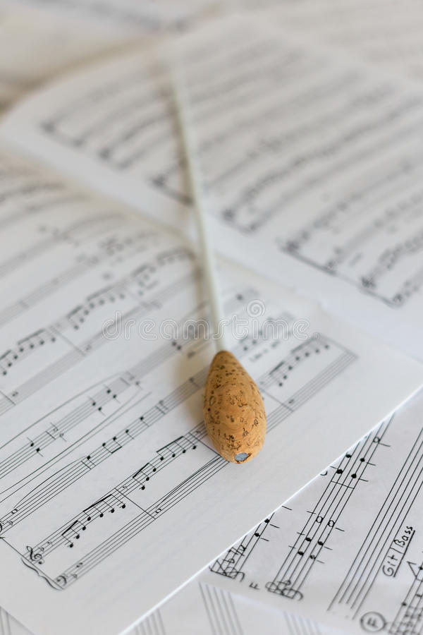 A natural conductors baton on orchestral score. A natural baton on sheet music stock photo
