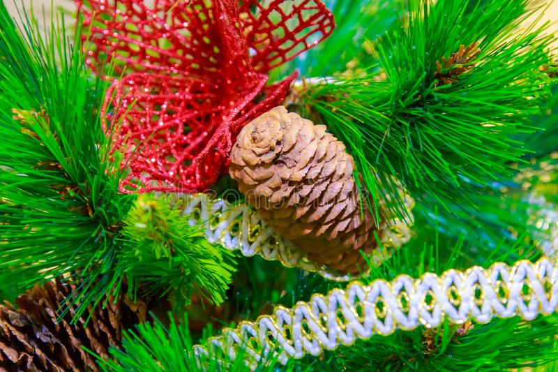 Natural cone decorates an artificial Christmas tree close royalty free stock image