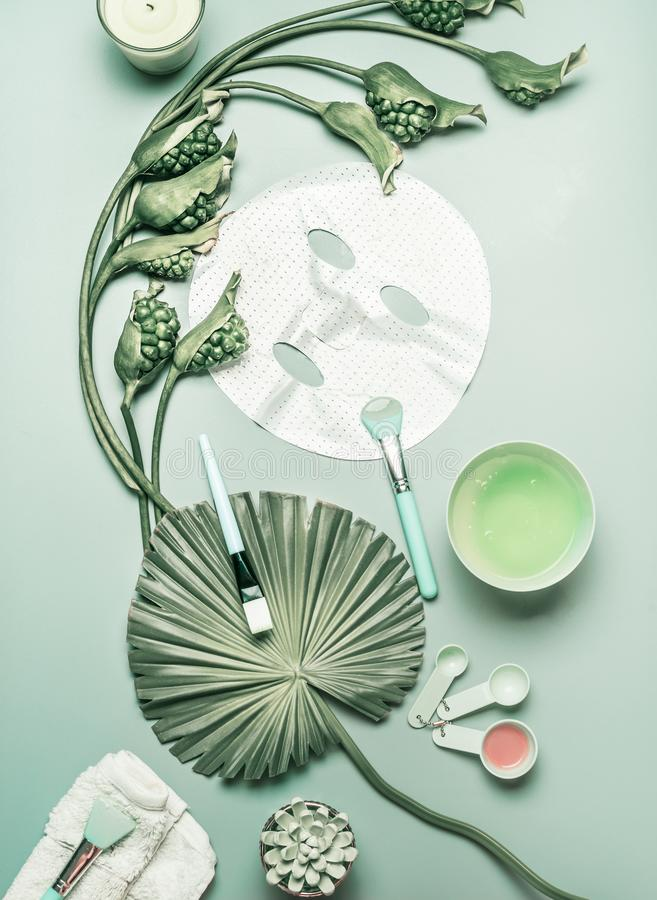 Natural cosmetic flat lay. Facial sheet mask for home facial skin care with flowers and green tropical leaves, top view, flat lay. royalty free stock image