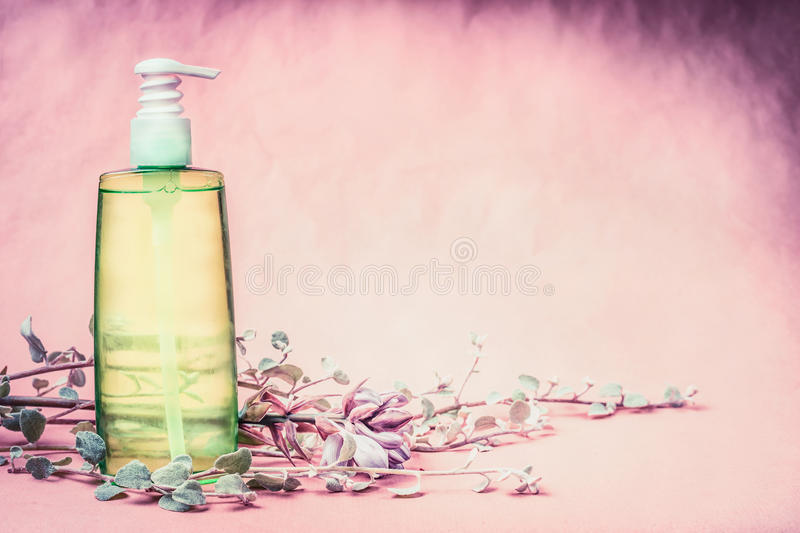 Natural cosmetic product bottle with green lotion or tonic liquid with fresh herbs and flowers at pink background. Healthy skin o. R body care, beauty , spa or stock photo