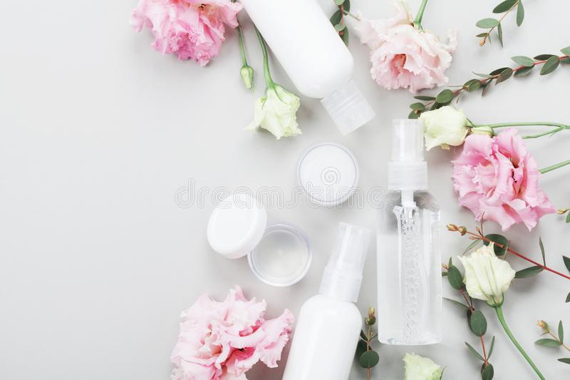 Natural cosmetic set from cream, lotion and moisturizer decorated flowers and green leaves on table top view. Flat lay style. stock photo
