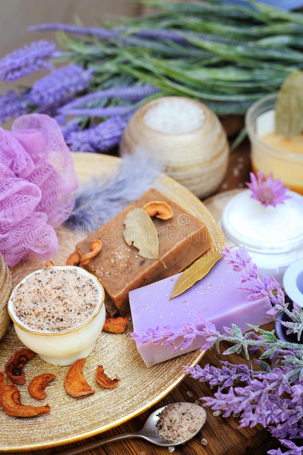 Natural cosmetics concept background - coffee and lavender artisan soap, salt scrub, cream and flowers stock images