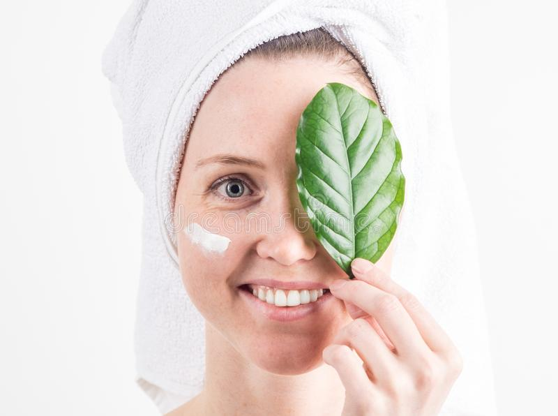Natural Cosmetics: a girl with a white towel on her head smiles and covers one eye with a green leaf. royalty free stock photography