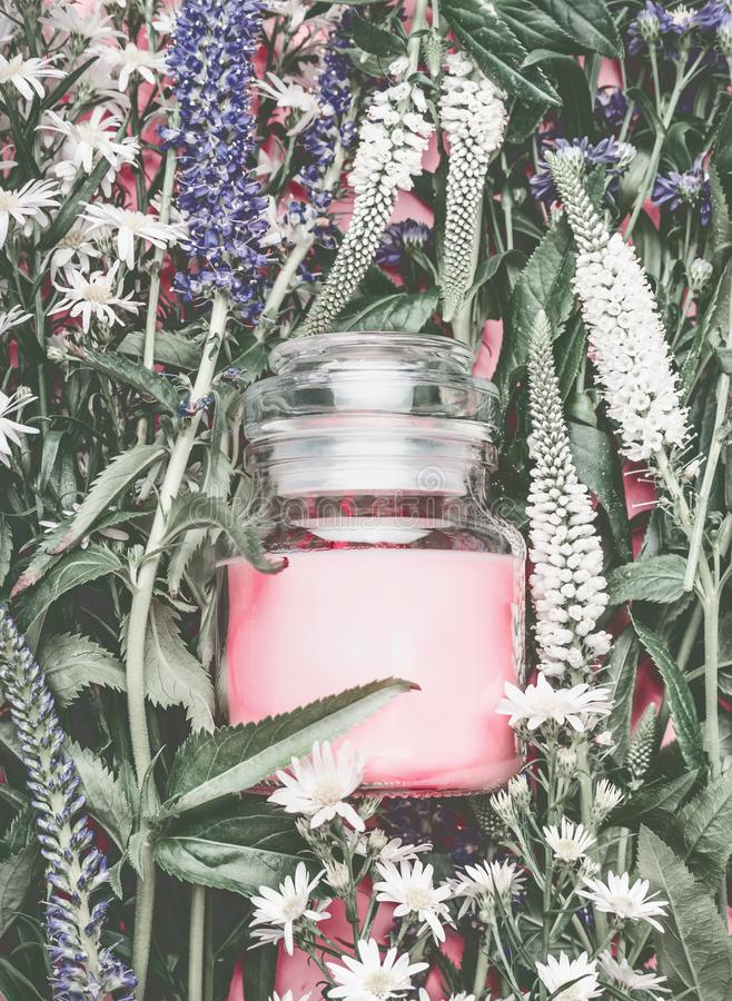 Natural cosmetics jar with pastel pink cream on herbal leaves and wild flowers, blank label for branding mock-up stock images