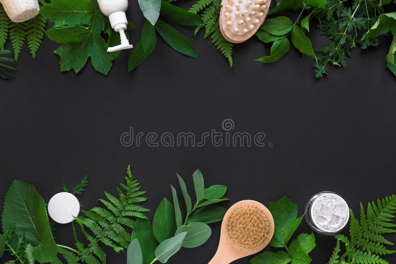 Natural cosmetics and leaves. Natural cosmetics and green leaves on black background, copy space. Natural organic skincare, bio research and healthy lifestyle royalty free stock images