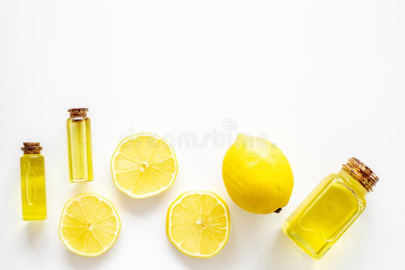 Natural cosmetics. Lemon essential oil near halfs os lemons on white background top view closeup space for text royalty free stock photography