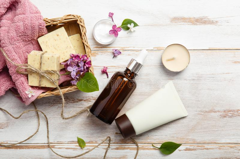 Natural cosmetics with lilac flowers. Serum, soap and cream with towel rolls. royalty free stock image
