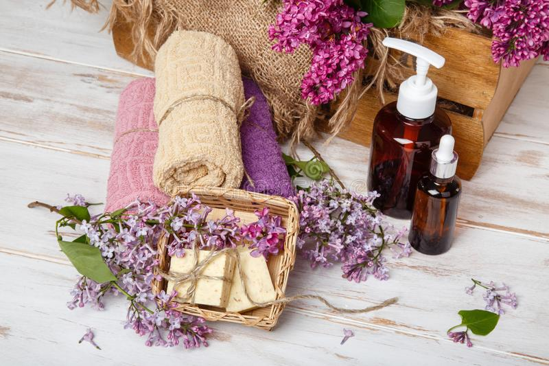 Natural cosmetics with lilac flowers. Serum, soap and cream with towel rolls. stock photos