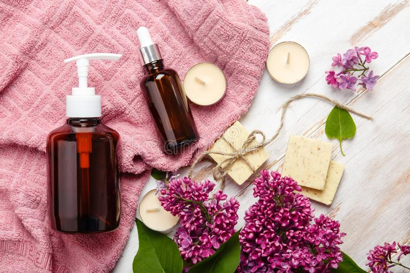 Natural cosmetics with lilac flowers. Serum, soap and cream with towel rolls. stock photography