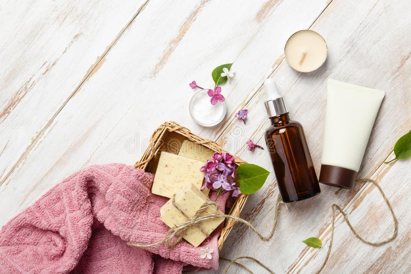 Natural cosmetics with lilac flowers. Serum, soap and cream with towel rolls. royalty free stock photo
