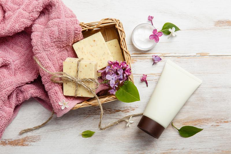 Natural cosmetics with lilac flowers. Set of cream and towel rolls. stock photography