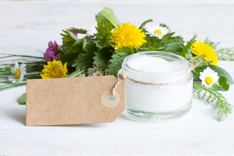 Natural cosmetics for skin care cream  eco label with herbs and flowers. On white royalty free stock photo