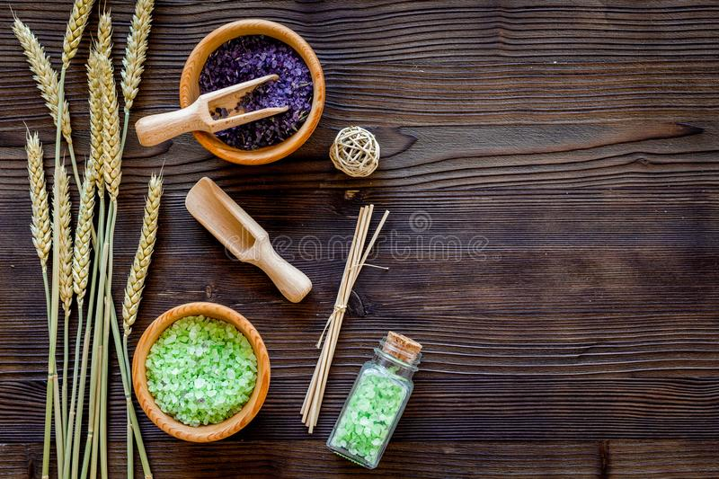 Natural cosmetics with wheat and herbs for homemade spa on wooden background top view mock up royalty free stock photography