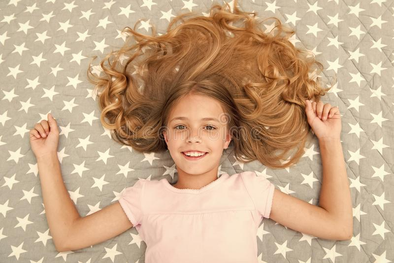 Natural curls treat and care. Girl child with long curly hair lay on bed top view. Child perfect curly hairstyle looks. Cute. Conditioner mask organic oil keep stock photos