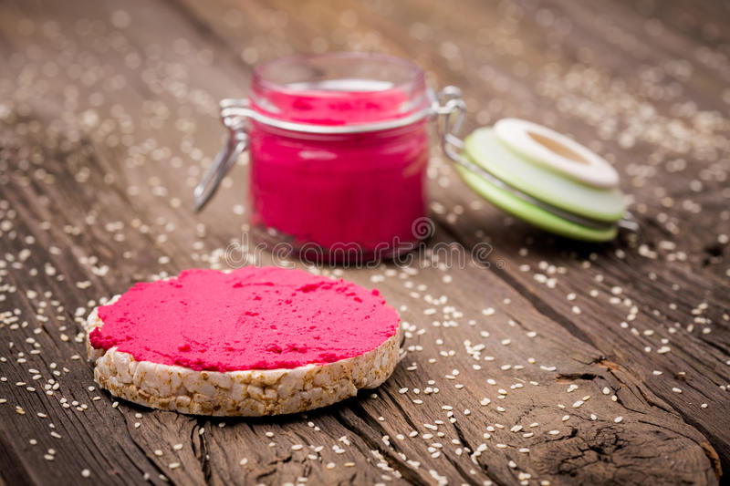 Natural diy homemade pink hummus. Homemade DIY natural vegan very healthy pink hummus of chickpeas and beetroot with rice wafle and in a glass jar on a wooden royalty free stock photography