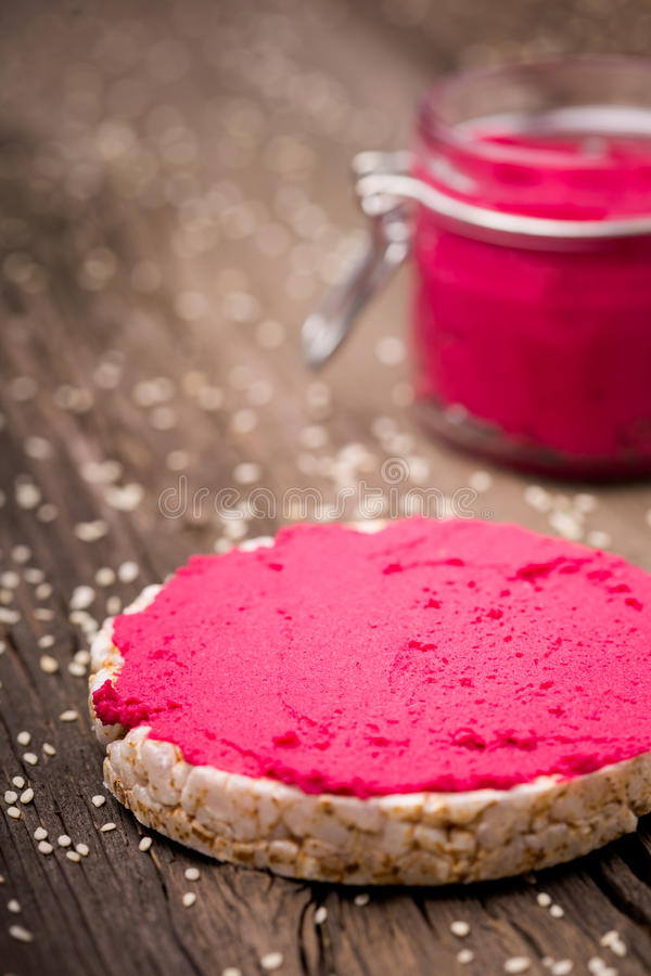 Natural diy homemade pink hummus. Homemade DIY natural vegan very healthy pink hummus of chickpeas and beetroot with rice wafle and in a glass jar on a wooden stock photo
