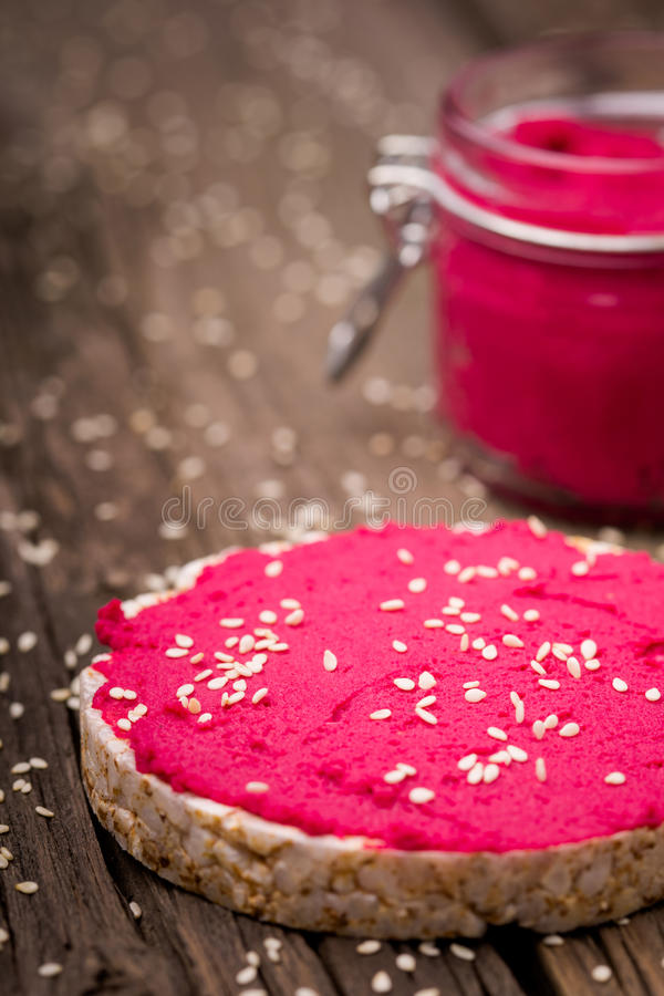 Natural diy homemade pink hummus. Homemade DIY natural vegan very healthy pink hummus of chickpeas and beetroot with rice wafle and in a glass jar on a wooden royalty free stock photos