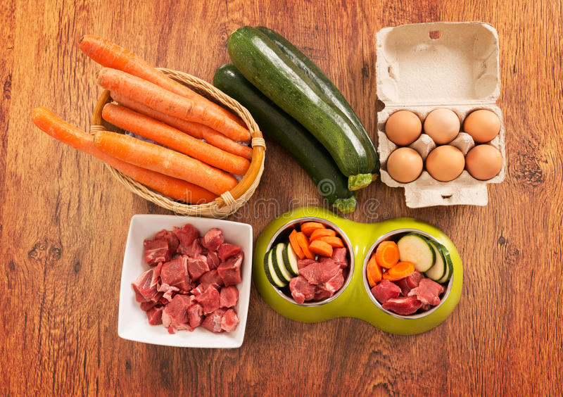 Natural dog food. Natural, organic dog's food in a bowl with ingredients zucchini, carrot, eggs and raw meat stock photos