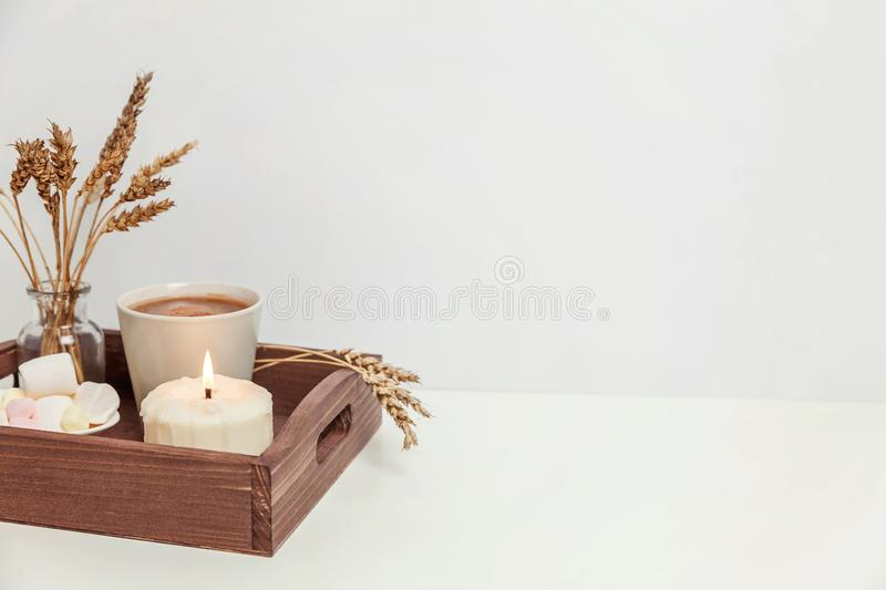 Natural eco home decor with cup coffee marshmallow and candle on wooden tray stock image