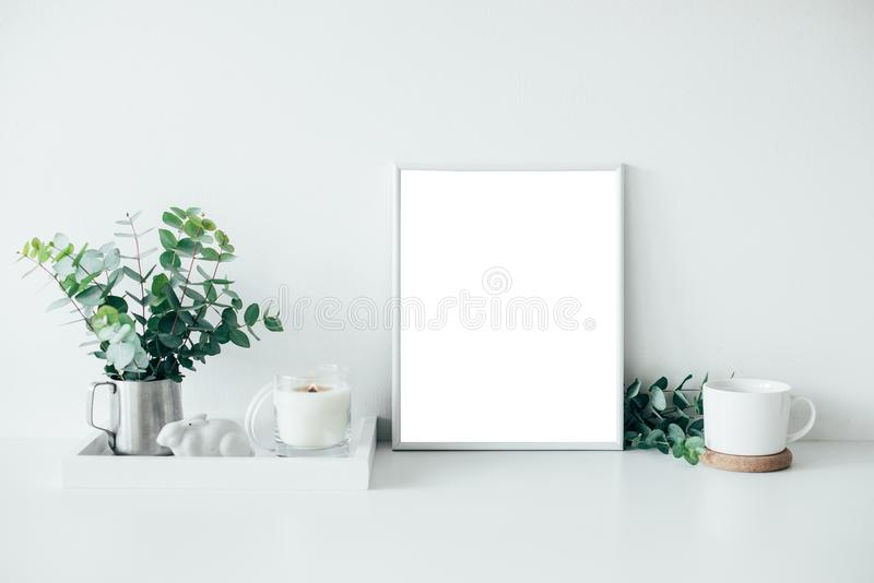 Natural eco home decor with green leaves, poster mock-up and bur. Ning candle on tray, boho interior decorations royalty free stock photography