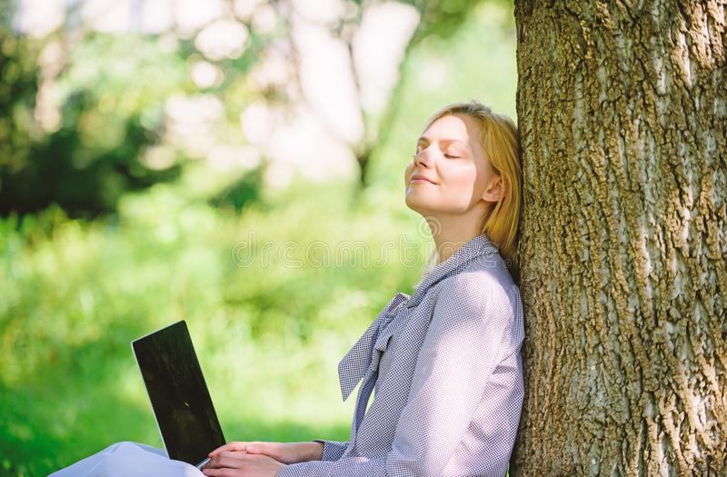 Natural environment office. Work outdoors benefits. Woman with laptop work outdoors lean tree. Minute for relax royalty free stock photos