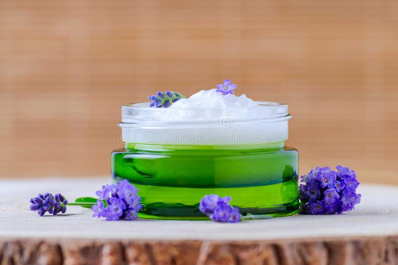 Natural face cream with fresh lavender flowers, selective focus, brown background. Natural face cream with fresh lavender flowers, organic cosmetics stock photo