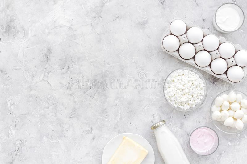 Natural farm products. Milk, cottage, eggs, cheese, yougurt on grey background top view copy space. Monochrome royalty free stock images