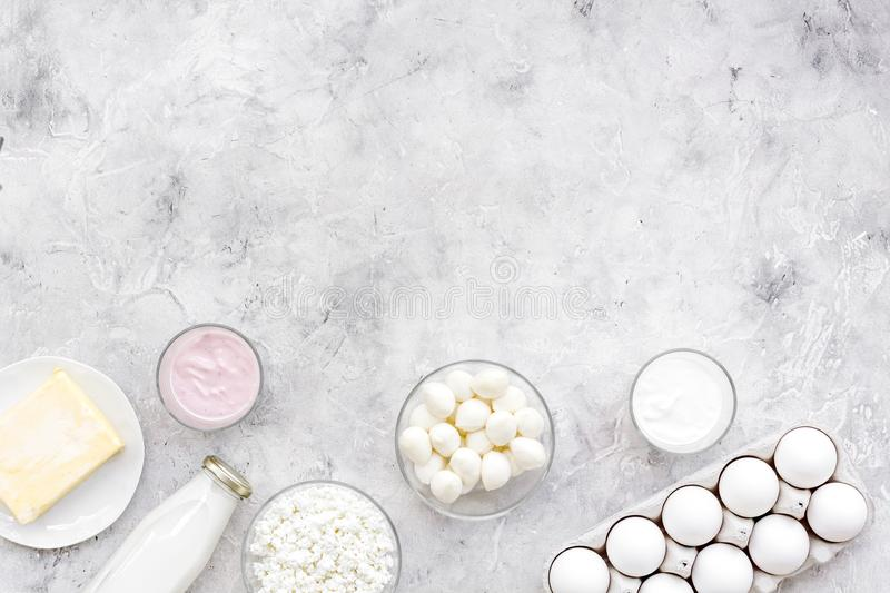 Natural farm products. Milk, cottage, eggs, cheese, yougurt on grey background top view copy space. Monochrome stock photo