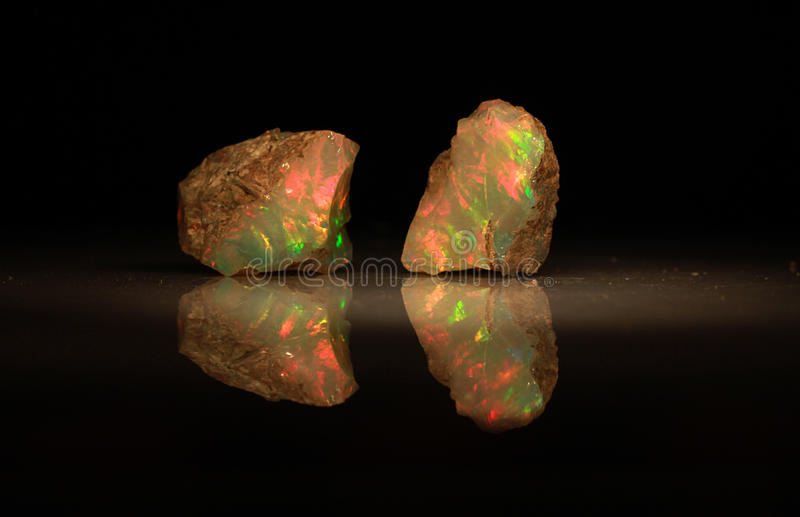 Natural fire play-of-colour opal Welo. Natural black play-of-colour opal - bright natural stone rough with yellow and red green indigo opalescence play-of-colour stock photo
