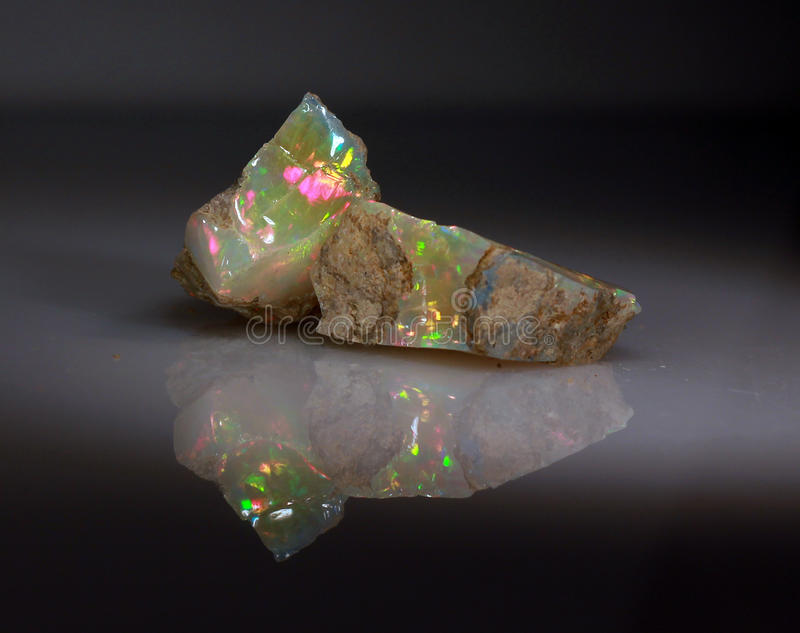 Natural fire play-of-colour opal Welo. Natural black play-of-colour opal - bright natural stone rough with yellow and red green indigo opalescence play-of-colour royalty free stock image