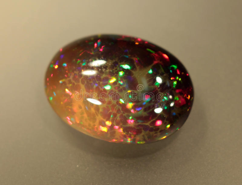 Natural fire play-of-colour opal Welo. Natural black play-of-colour opal - bright natural stone rough with yellow and red green indigo opalescence play-of-colour stock images