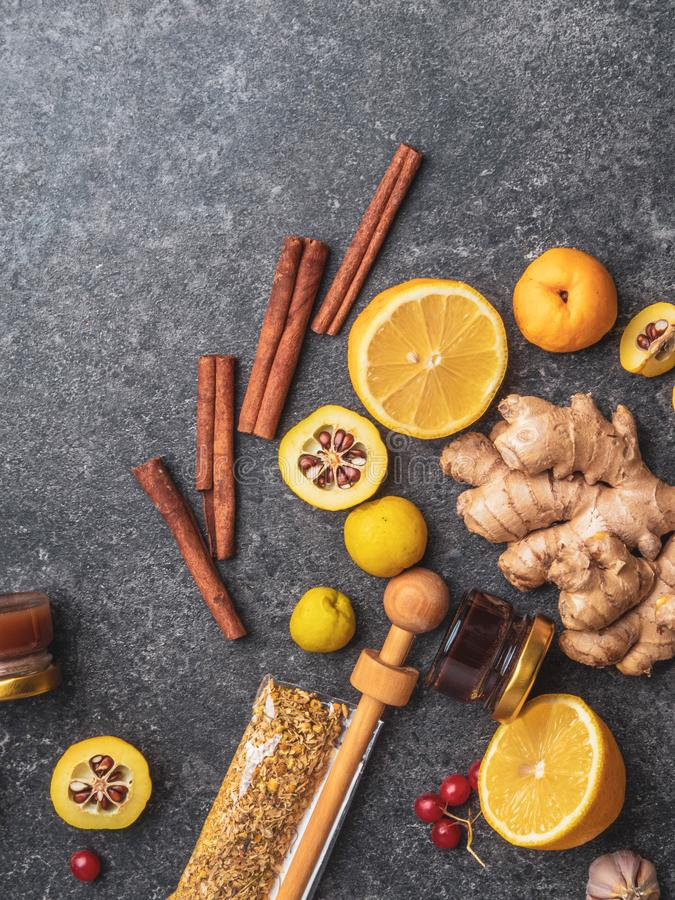 Natural flu and cold remedy ingredients, chamomile flowers, cinnamon sticks, ginger, lemon, honey, cydonia, propolis, garlic Flat royalty free stock image