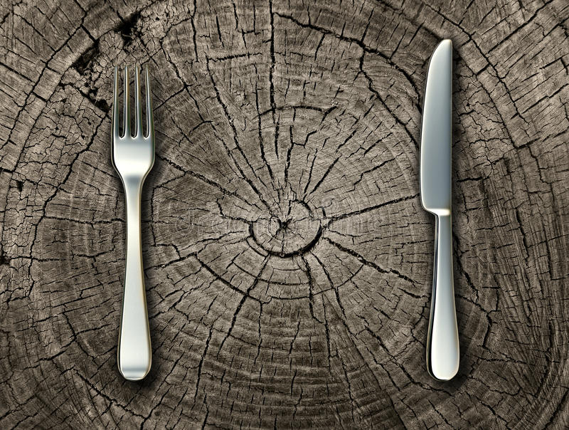 Natural Food. Concept and organic eating healthy lifestyle idea with a silver fork and knife on a cut tree stump log representing raw food and rustic country