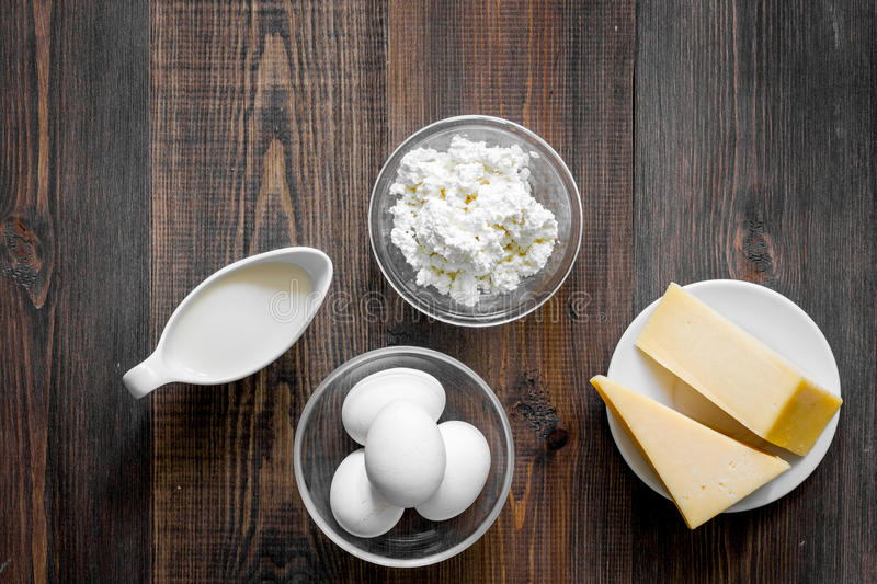 Natural food. Milk, cottage, cheese, eggs on dark wooden background top view copyspace stock image