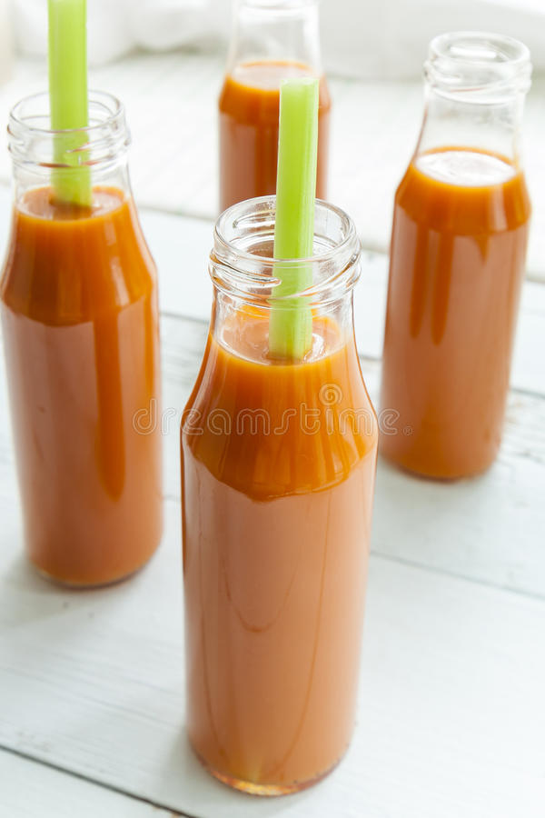 Natural and fresh carrot juice in small bottles with fresh celery stock photos