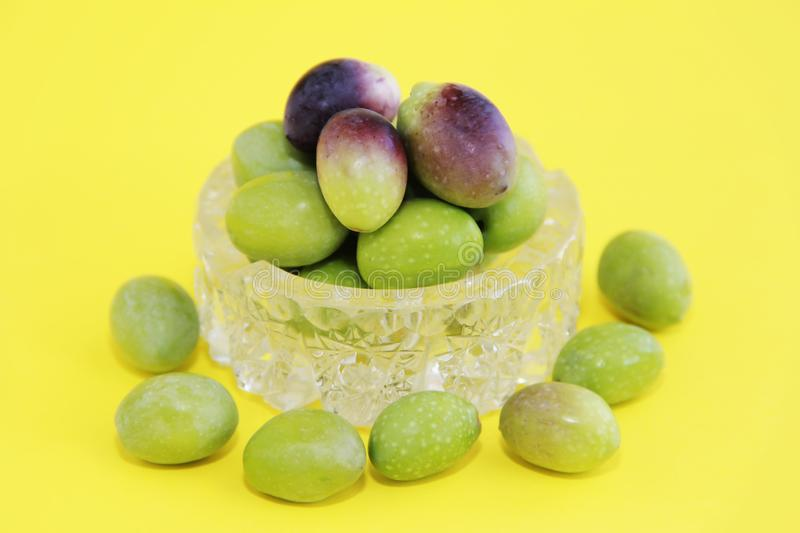 Natural fresh round green and brown olives in a decorative glass plate on a yellow background royalty free stock photos
