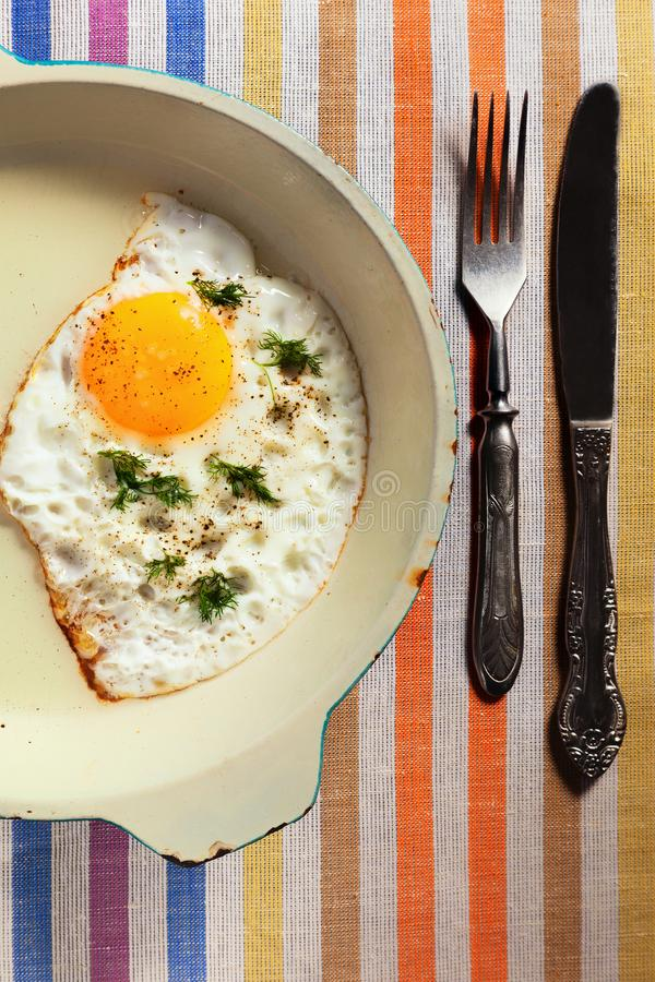 Natural fried egg on an old frying pan with an old knife and for royalty free stock images