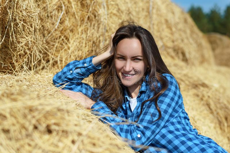 Natural frontal portrait of a smiling young woman standing leaning on a haystack royalty free stock images