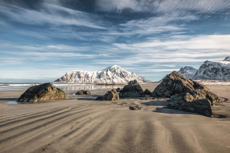 Natural furrow sand with snow mountain and blue sky at Skagsanden beach. Lofoten, Norway royalty free stock photography