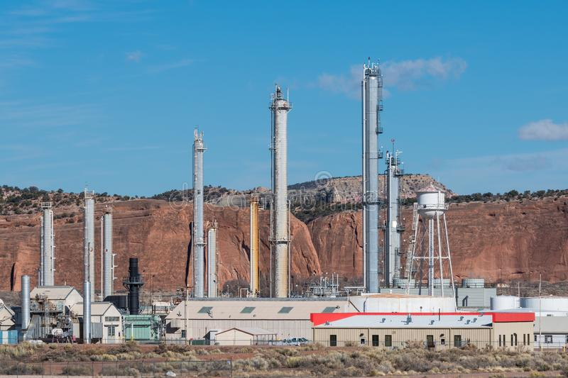 A natural gas refinery contrasted with the natural red rock landscape of the southwestern United States. A natural gas refinery and red rock cliffs near Gallup royalty free stock image